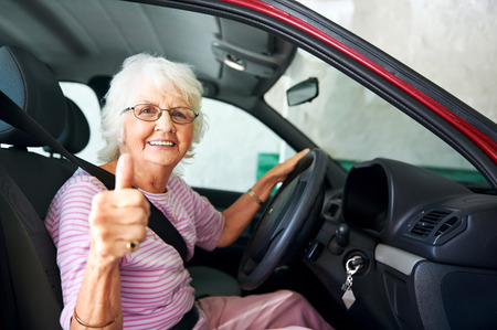 woman driving car: An positive older woman sitting in a car showing a thumbs up