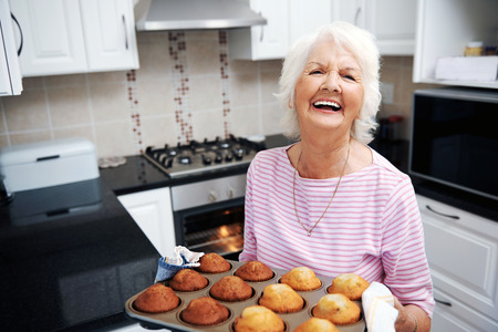 A laughing pensioner holding a tray of baked muffins just out of the oven photo