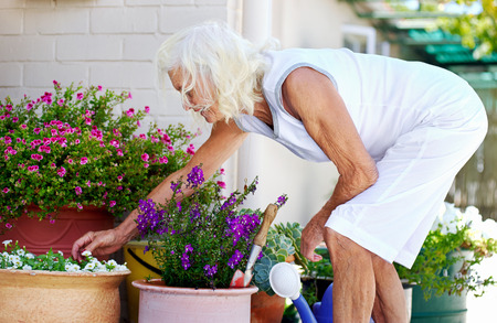 An elderly woman working on her flower pot outside her house photo
