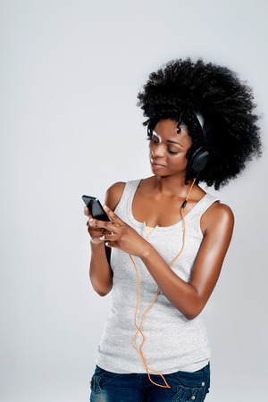 relaxed woman: Smiling black female with afro listening to music off her phone against isolated