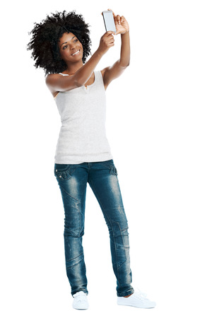 Studio shot of attractive african woman with afro taking a picture of herself with her camera phone photo