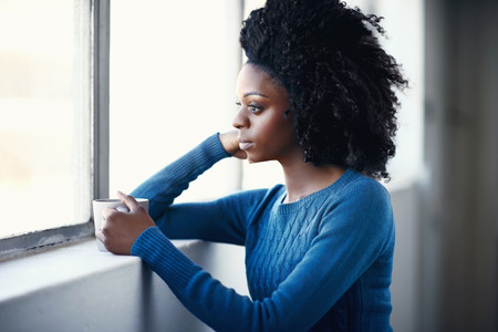 contemplative: Beautiful african female with afro holding a hot beverage while looking out a window