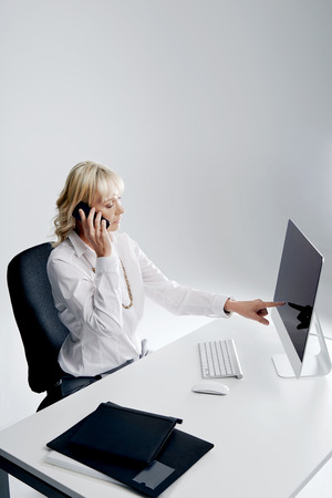 Corporate woman at her desk talking on her cellphone pointing at her computer screen photo