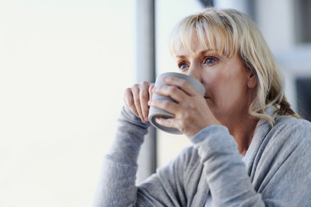 contemplative: Beautiful blonde woman sipping a cup of tea while looking out the window