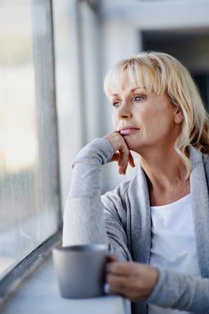 Krásná žena hledá z okna s horkou nápoj