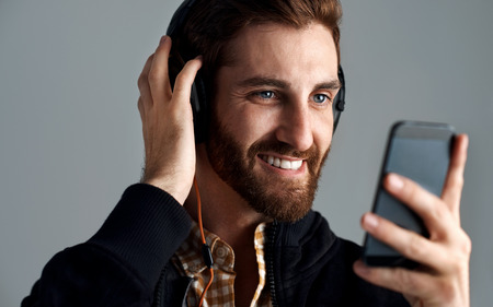streaming: Man with headphones streaming music online with phone enjoying song with beard