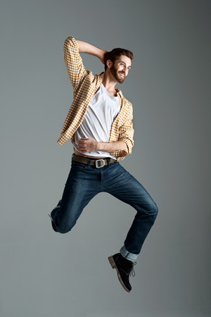 male fashion model: Fashion model man with hipster beard jumping and having fun in studio