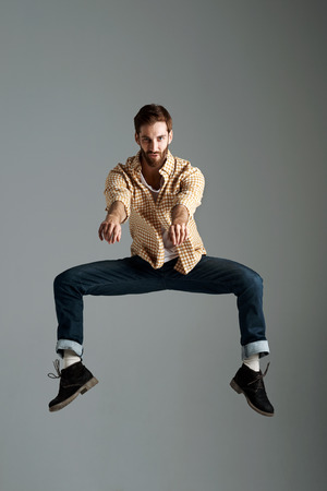 Fashion model man with hipster beard jumping and having fun in studio photo
