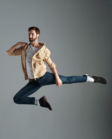 dance pose: Fashion model man with hipster beard jumping and having fun in studio