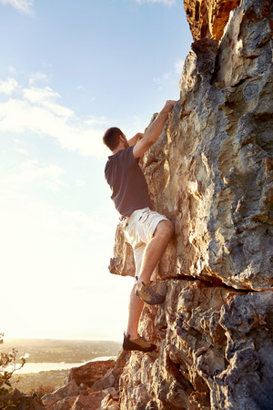 rockclimber: Rockclimber climbing up a steep piece of mountain with copyspace
