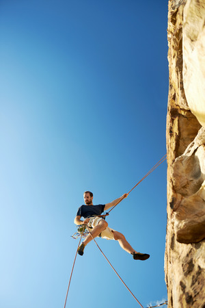 A rockclimber going down a steep mountain with a rope against a blue sky