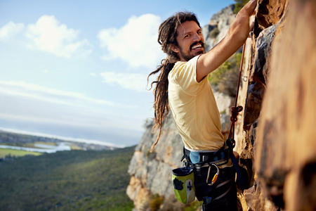 A rockclimbing man with dreadlocks smiling at the camera while climbing up a steep mountain with a harness photo
