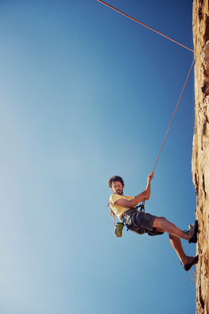 rapelling: A man with dreadlocks in climbing gear rapelling down a mountain against a blue sky with rope with copyspace Stock Photo