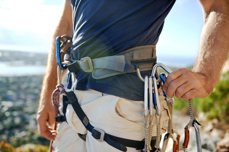 Close up of a man in his harness and rockclimbing equipment Imagens