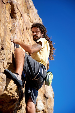 rockclimber: A rockclimber finding a foothold on the steep mountain hes climbing