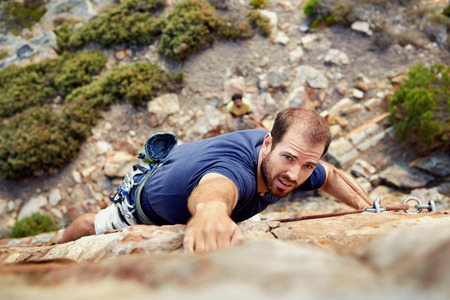 A man reaching for a grip while he rock climbs on a steep cliff