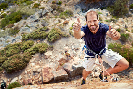 rockclimber: A rockclimber with rockclimbing equipment on holding a thumbs up and smiling at  the camera