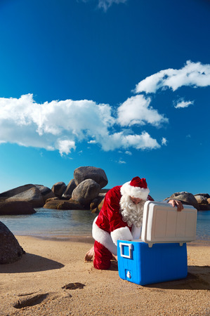 Father Christmas taking something out of his Cooler while relaxing on the beach on holiday photo