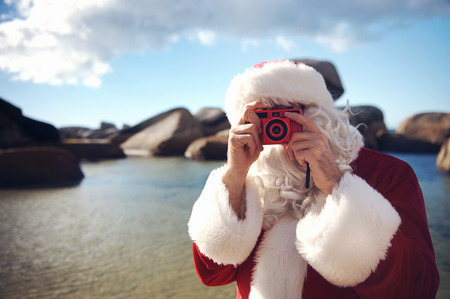 Father Christmas on a beach taking a picture with copyspace photo