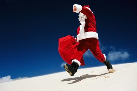 botas de navidad: Santa Claus caminando por una duna de arena en una playa
