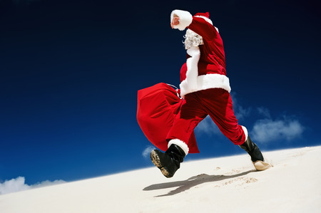 christmas in july: Santa Claus walking down a sand dune on a beach Stock Photo