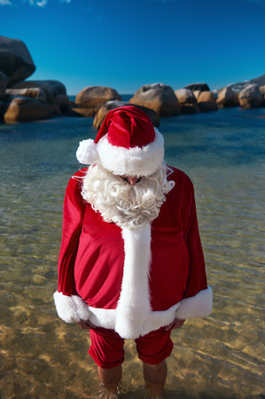 out of context: Out of context shot fo father Christmas at the ebach with his feet in the water relaxing