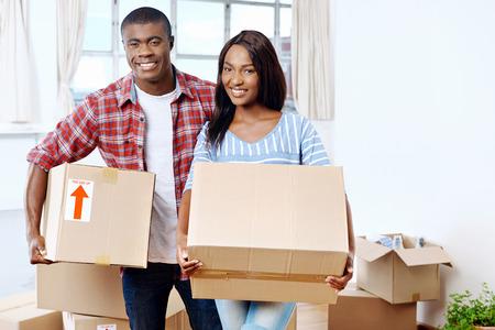 Mladí Černoch pár stěhování boxy do nového domova společně dělat úspěšný život Reklamní fotografie
