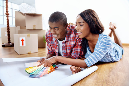 young african couple having fun deciding on paint colour swatch for new home apartment 写真素材