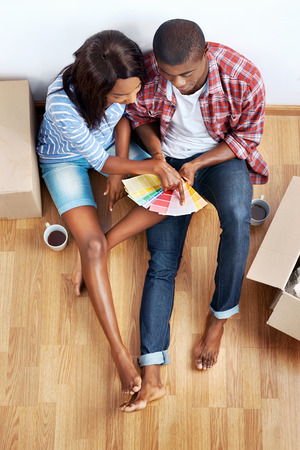 buying a house: overhead view of young black african couple with moving boxes in new apartment choosing colour of paint for walls