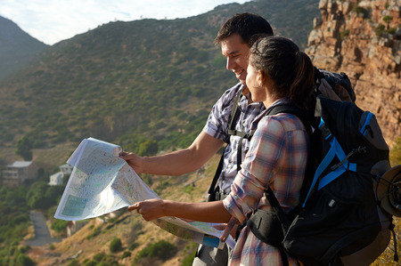 Smiling couple with backpacks on hiking trail looking at map photo