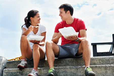 takeaway: A happy couple sitting together in fitness clothing having their takeaway meals on the docks