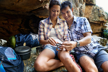 replenishing: A hiker couple sitting together and taking a break by a cave while holding a part of their gas burner stove