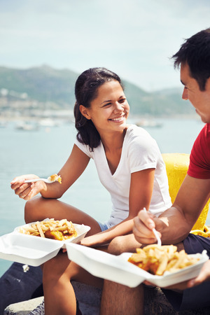 eating out: A beautiful woman smiling at her partner as they eat fish and chips by the harbour