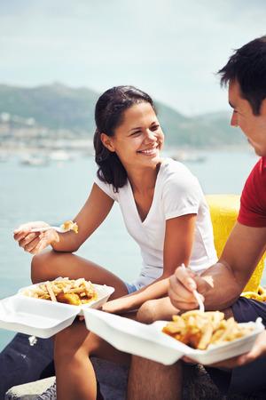 fish and chips: Una bella mujer sonriendo a su pareja, ya que comer pescado y patatas fritas en el puerto Foto de archivo