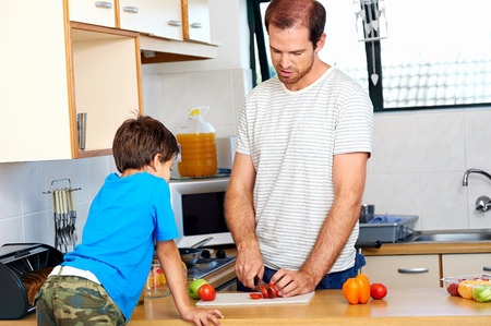 single dad in kitchen with son chopping healthy food for lunch photo
