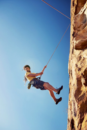 rapelling: A man with dreadlocks in climbing gear rapelling down a mountain against a blue sky with rope