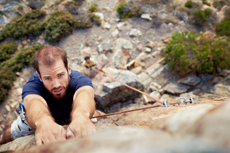 other keywords: A man holding on to a piece of rock while he climbs up a steep cliff with copyspace