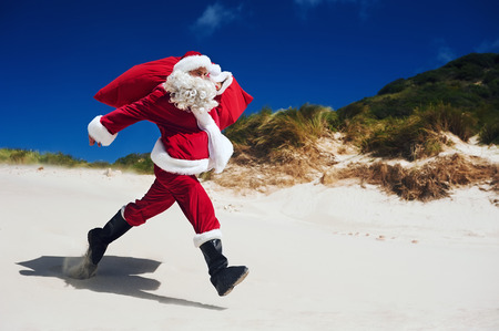 out of context: Santa Claus walking along the beach in an out of context situation