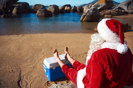 christmas in july: Father Christmas relaxing on the beach resting his bare feet on his cooler while looking at the view Stock Photo