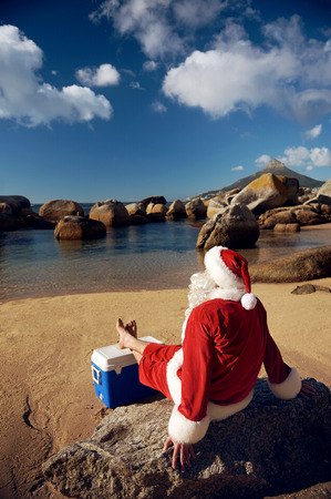 Santa Claus relaxing on the beach resting his bare feet on his cooler while looking at the view photo