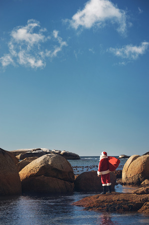 out of context: Santa Claus out of context on a beach looking at the view of the ocean with copyspace