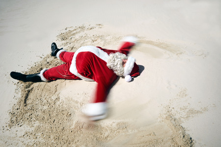 A carefree Father Christmas doing a sand angel on the beach sand with copyspace