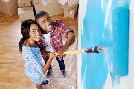 painting and decorating: high overhead view of young black couple painting wall with roller in new house
