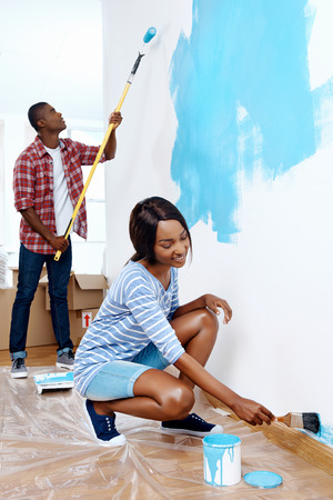 man painting: Fresh coat of paint on new apartment for young black african couple who have success and a home