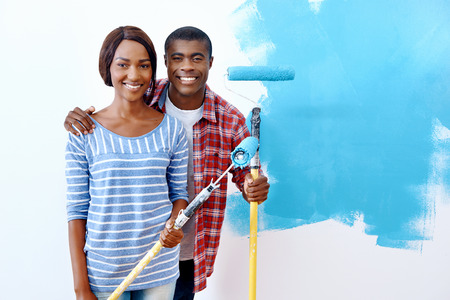 painting and decorating: Fresh coat of paint on new apartment for young black african couple who have success and a home