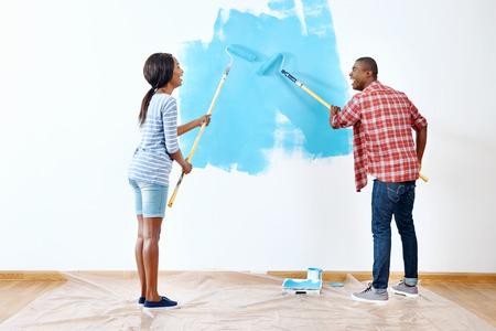 成功と家を持っている若いの黒アフリカのカップルのための新しいアパートに塗料の新鮮なコート 写真素材