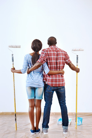 new: Young black couple ready to paint their new home apartment together