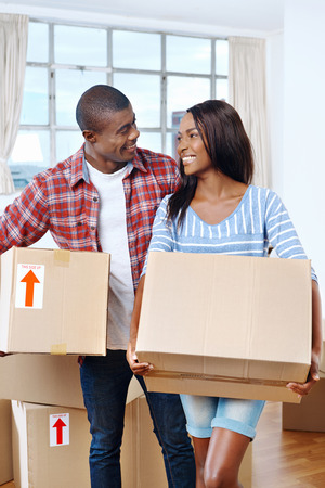 young black african couple moving boxes into new home together making a successful life Reklamní fotografie