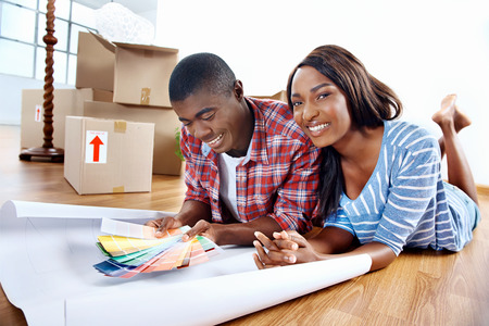 young african couple having fun deciding on paint colour swatch for new home apartment 스톡 콘텐츠