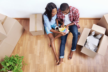 home buying: overhead view of young black african couple with moving boxes in new apartment choosing colour of paint for walls